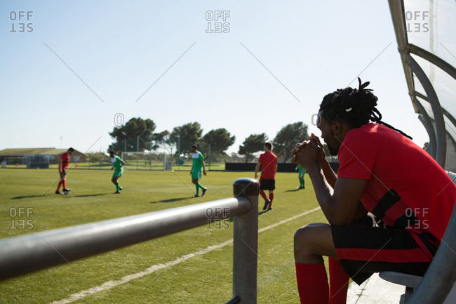 Side view of player watching the football match from dugout
