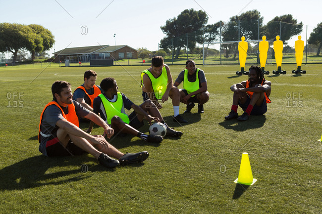 Soccer players relaxing on sports field