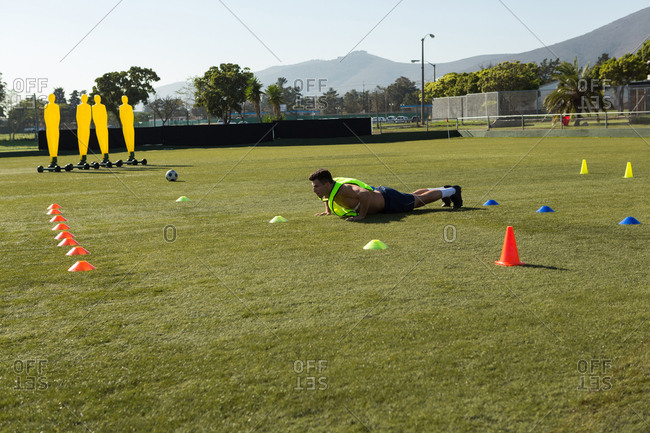 Player doing push up in the field on a sunny day