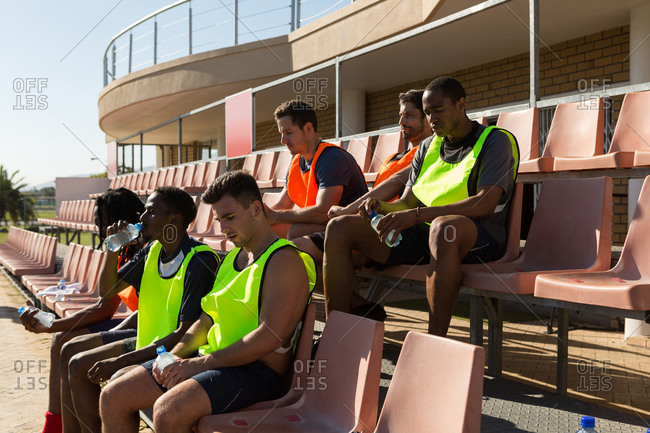 Football players relaxing on dugout
