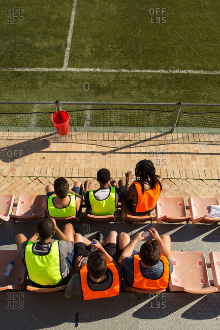 High angle view of football players relaxing on dugout