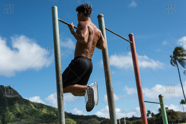 Young man exercising on horizontal bar in the park