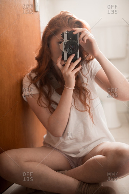 Woman clicking photo with camera at home
