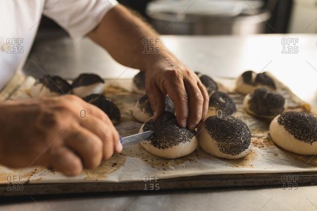 Male baker preparing round croissants in bakery shop