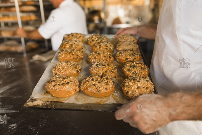 Mid section of male baker holding tray of baked sweet foods
