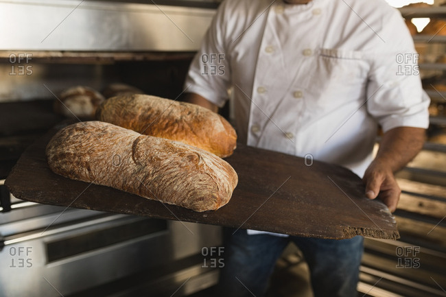 Mid section of male baker holding baked bread in bakery shop