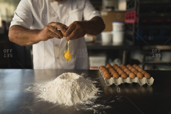 Mid section of male baker preparing dough in bakery shop
