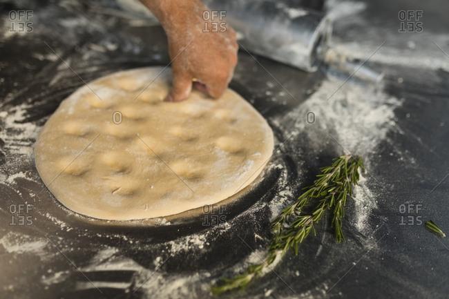 Male baker kneading a dough in bakery shop