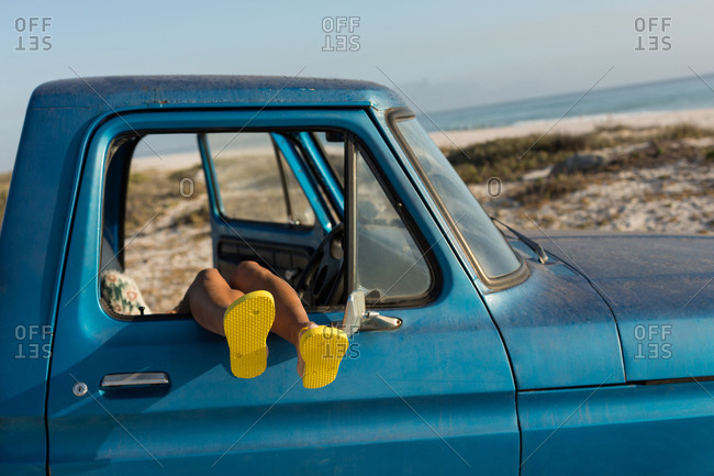 Woman relaxing with feet up in a pickup truck at beach