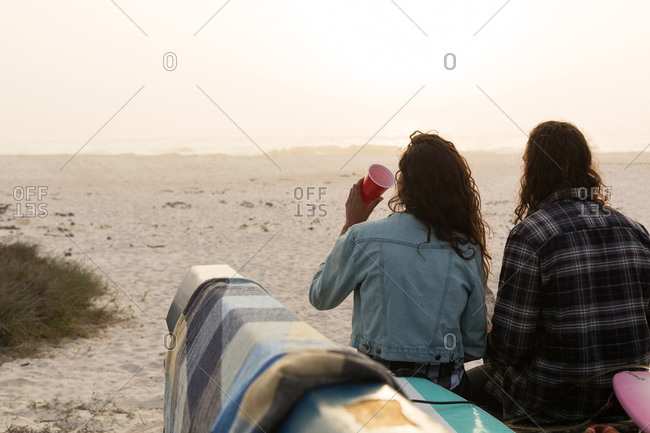 Rear view of couple having drink on a pickup truck in the beach