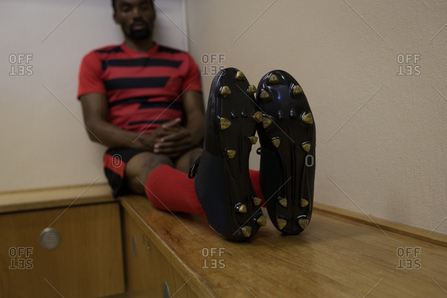 Football player relaxing on bench in dressing room