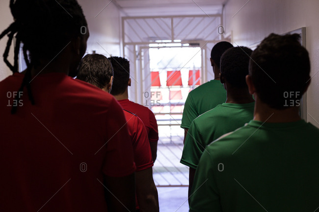 Rear view of football players leaving the dressing room