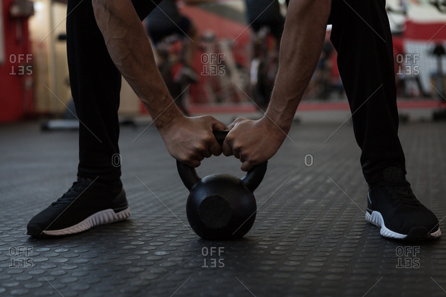 Athlete exercising with kettlebell in gym