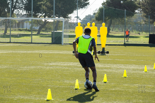 Soccer player dribbling through cones in sports field