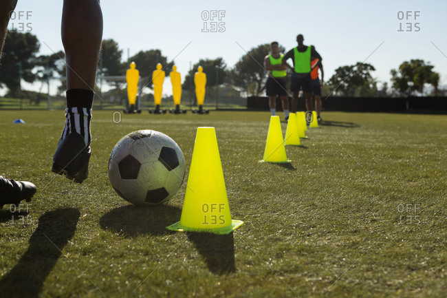 Soccer player dribbling the ball through cones in sports field
