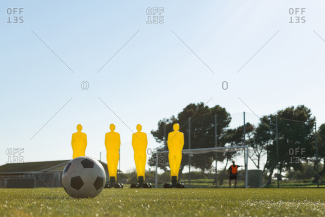 Football training equipment and soccer ball in field on a sunny day