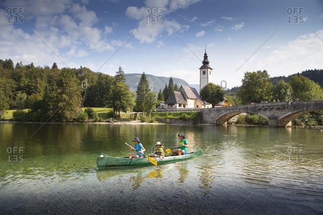 September 4, 2016: Family in canoe on Lake Bohinj, with church and bridge of Ribcev Laz in background, Triglav, Slovenia