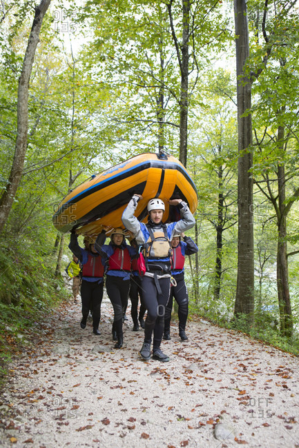 September 6, 2016: Group of rafters carrying inflatable boat over their heads to river Soca near Bovec, Triglav, Slovenia