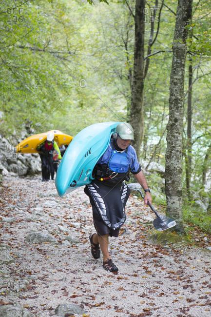 September 6, 2016: Kayakers carrying their colorful kayaks to river Soca near Bovec, Triglav, Slovenia
