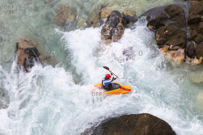 September 6, 2016: Male kayaker crossing whirlpool in green colored Soca river near Bovec, Slovenia