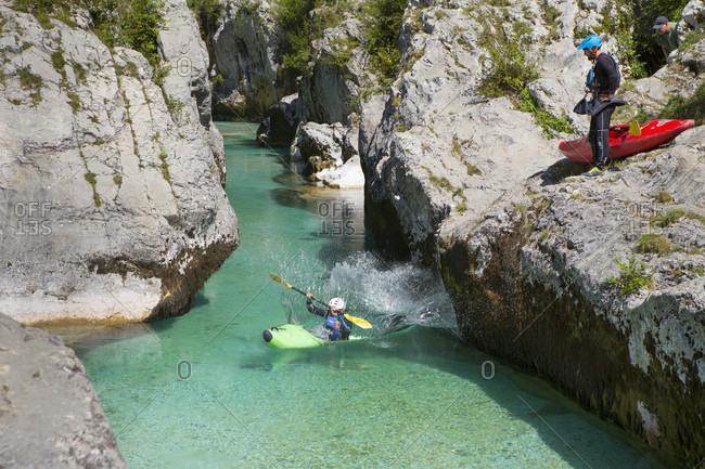 September 8, 2016: A man in a kayak is jumping into the water, while another man is watching. The emerald Soca near Bovec in Slovenia, originating in the Triglav mountains, is famous for all kinds of white water activities.