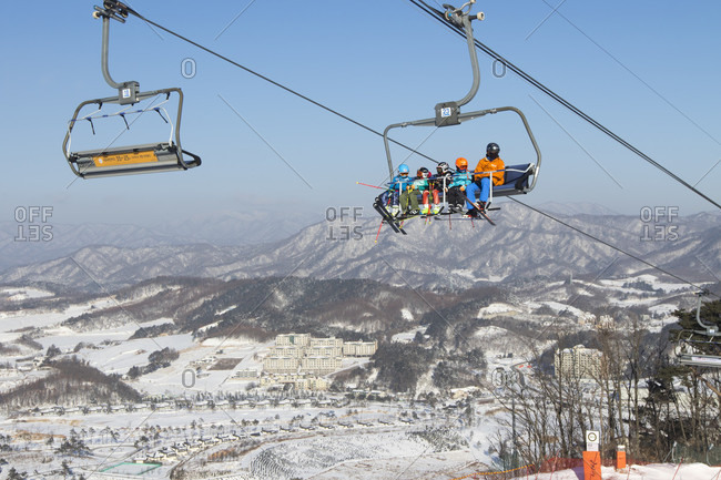 January 22, 2017: Colorful dressed skiers in a chair lift high above Alpensia resort in the Gangwon-do region of South Korea.  The Alpensia Resort is a ski resort and a tourist attraction. It is located on the territory of the township of Daegwallyeong-myeon, in the county of Pyeongchang, hosting the Winter Olympics in February 2018.  The ski resort is approximately 2.5 hours from Seoul or Incheon Airport by car, predominantly all motorway.   Alpensia has six slopes for skiing and snowboarding, with runs up to 1.4 km (0.87 mi) long, for beginners and advanced skiers, and an area reserved for snowboarders. While the resort is open year-round, the off-season turns the bottom of the slopes into a wild flower garden estimating 100,000-square meters.