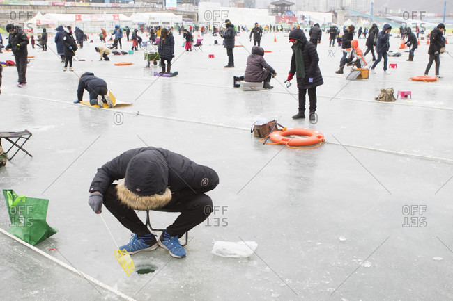 January 20, 2017: People are waiting above a hole in the ice during the ice fishing festival at Hwacheon Sancheoneo in the Gangwon-do region of South Korea.  The Hwacheon Sancheoneo Ice Festival is a tradition for Korean people. Every year in January crowds gather at the frozen river to celebrate the cold and snow of winter. Main attraction is ice fishing. Young and old wait patiently over a small hole in the ice for a trout to bite. In tents they can let the fish grilled after which they are eaten. Among other activities are sledding and ice skating.  The nearby Pyeongchang region will host the Winter Olympics in February 2018.