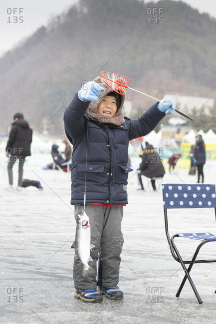 January 20, 2017: A young boy is happy with the fish he caught during the ice fishing festival at Hwacheon Sancheoneo in the Gangwon-do region of South Korea.  The Hwacheon Sancheoneo Ice Festival is a tradition for Korean people. Every year in January crowds gather at the frozen river to celebrate the cold and snow of winter. Main attraction is ice fishing. Young and old wait patiently over a small hole in the ice for a trout to bite. In tents they can let the fish grilled after which they are eaten. Among other activities are sledding and ice skating.  The nearby Pyeongchang region will host the Winter Olympics in February 2018.