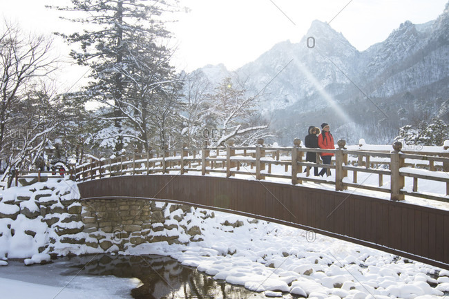 January 21, 2017: A man and woman are walking over a wooden bridge in Seoraksan National Park, Gangwon-do, South Korea.  Seoraksan is a beautiful and iconic National Park in the mountains near Sokcho in the Gangwon-do region of South Korea. The name refers to Snowy Crags Mountains. Set against the landscape are two Buddhist temples: Sinheung-sa and Beakdam-sa. This region is hosting the winter Olympics in February 2018.