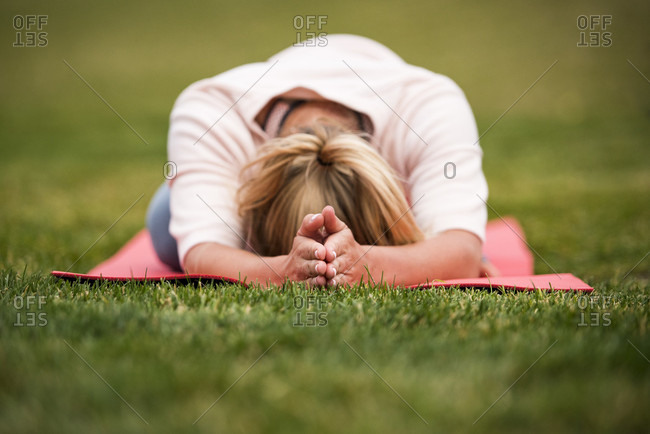 September 18, 2016: A young athletic blonde woman in her twenties enjoying yoga on a bright red mat in the grass of Jackson, Wyoming, USA