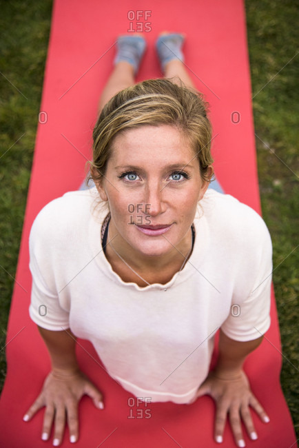 September 18, 2016: A young athletic blonde woman in her twenties enjoying yoga on a bright red mat in the grass and looking at camera, Jackson, Wyoming, USA