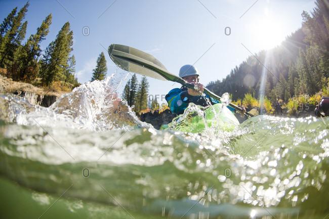September 20, 2016: Sun shining over female kayaker paddling along Snake River, Jackson, Wyoming, USA