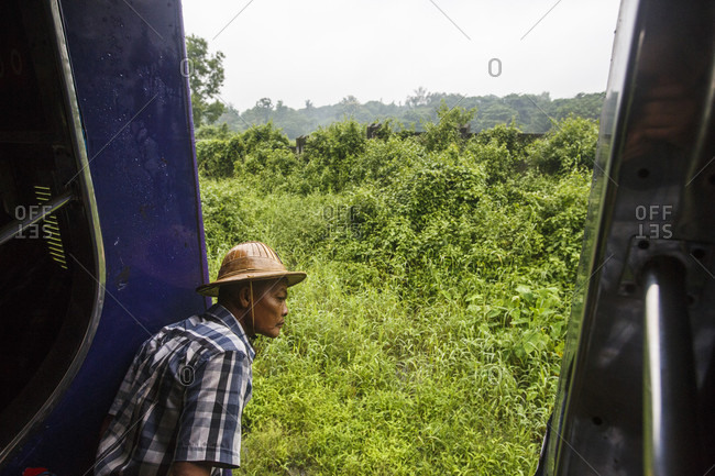 July 26, 2017: Passenger on Yangon Central Railway train looking at passing countryside, Yangon, Myanmar