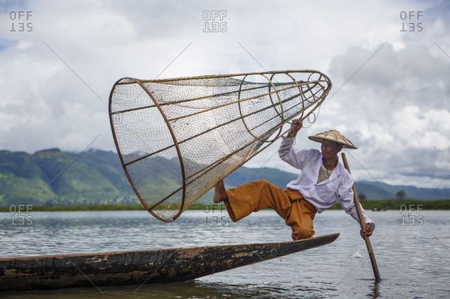 July 16, 2017: Fisherman wearing traditional clothing balancing in rowboat with fishing basket and paddle, Shan State, Myanmar