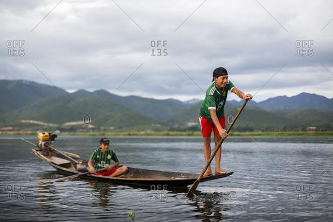 July 15, 2017: Two boys paddling in boat across Inle Lake, Shan State, Myanmar
