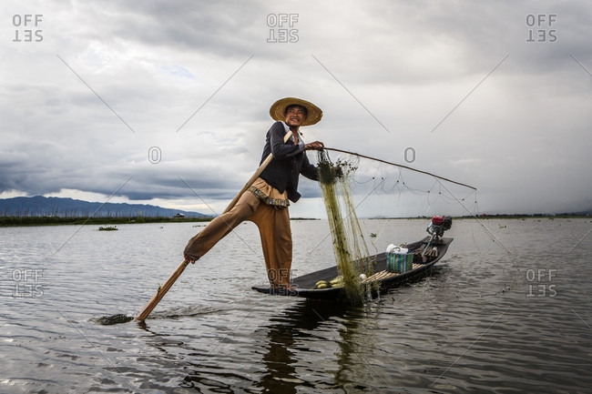July 15, 2017: Fisherman smiling at camera while balancing on motorboat with fishing rod and net, Shan State, Myanmar