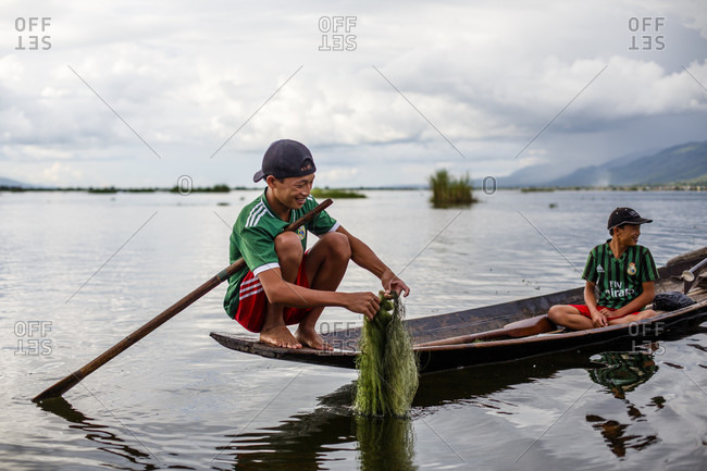 July 15, 2017: Two boys fishing with fishing nets in Inle Lake, Shan State, Myanmar