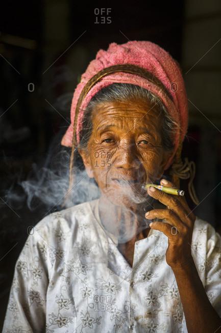 July 15, 2017: Portrait of senior woman looking at camera while smoking cheroot cigar, Shan State, Myanmar