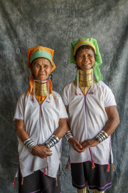 July 14, 2017: Portrait of two adult women wearing traditional neck rings posing together against gray fabric, Shan State, Myanmar