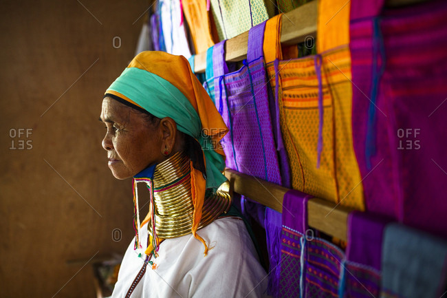 July 14, 2017: Portrait of senior woman wearing traditional neck rings standing beside colorful clothes hanging on wooden beams, Shan State, Myanmar