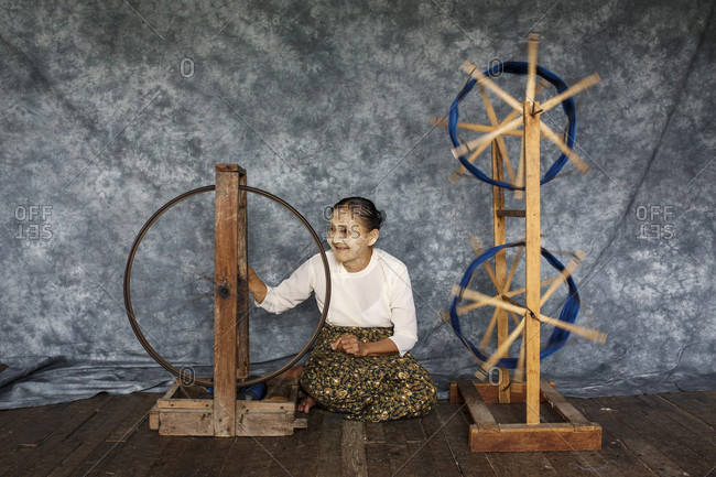 July 14, 2017: Senior woman sitting on wooden floor and weaving silk on spinning wheels, Shan State, Myanmar