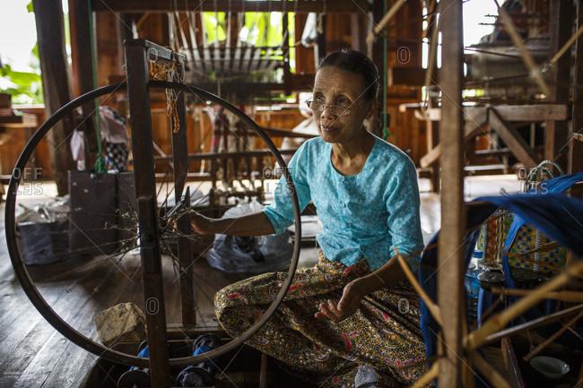 July 14, 2017: Senior woman weaving silk on spinning wheel inside house, Shan State, Myanmar