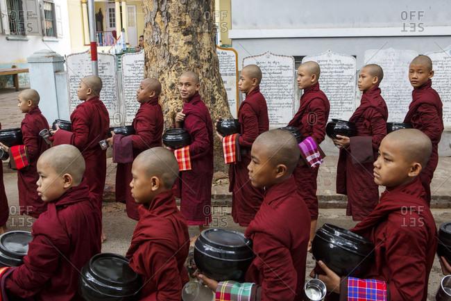 July 2, 2017: Young monks walking in rows and carrying bowls at Mahagandhayon Monastery, Amarapura, Myanmar