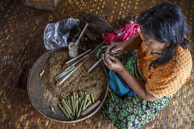 July 14, 2017: Adult woman sitting indoors and rolling traditional cheroot cigars, Shan State, Myanmar