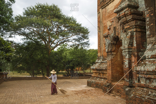 July 1, 2017: Person sweeping pavement around ancient temple, Bagan, Myanmar