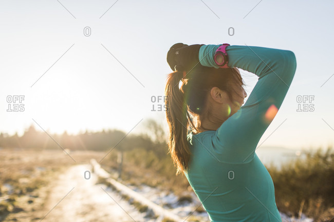 December 2, 2014: Female runner resting with hands behind head, Discovery Park, Seattle, Washington State, USA