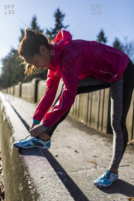 December 2, 2014: Female runner tying shoes on bridge, Seattle, Washington State, USA