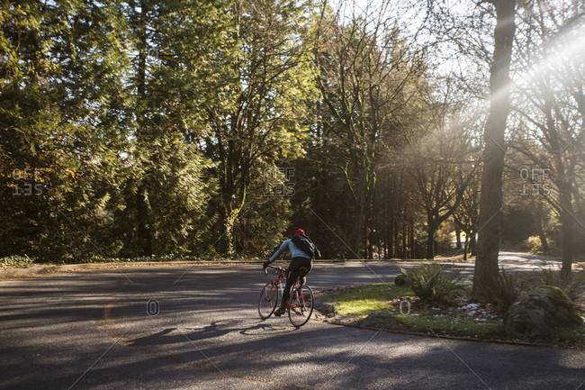 December 2, 2014: Man cycling on road surrounded by trees, Seattle, Washington State, USA