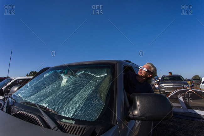 August 21, 2017: Man watching solar eclipse from car, August 8, 2017, Maupin, Oregon, USA