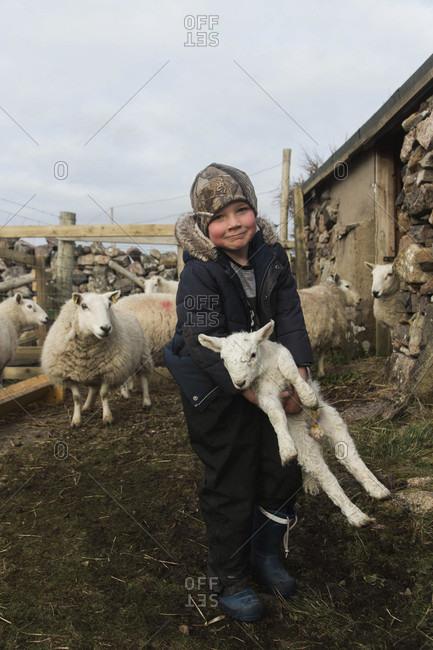 April 22, 2017: Portrait of farm boy holding lamb and looking at camera, Scotland, UK